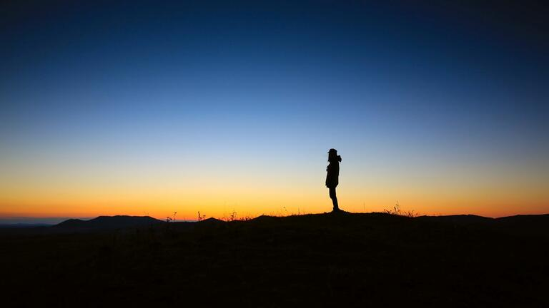 Person silhouetted against dawn sky