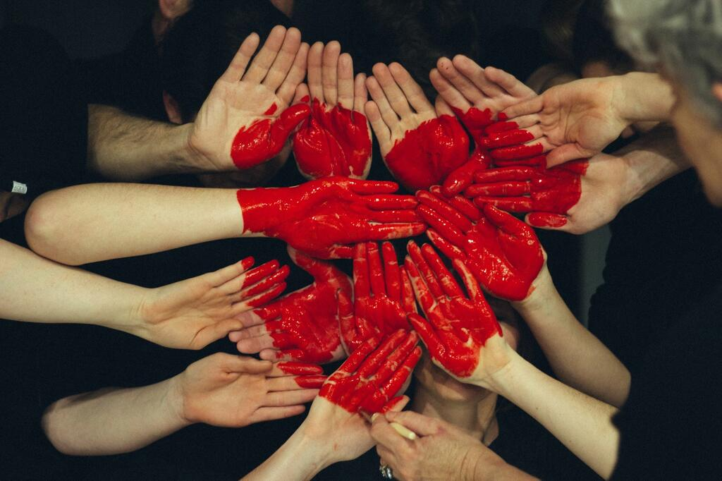 Heart made of red painted hands